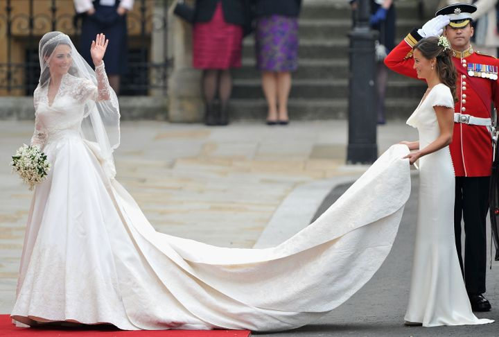 Kate waves to the crowds as her sister and maid of honor, Pippa Middleton, holds her dress before walking in to Westminster Abbey.