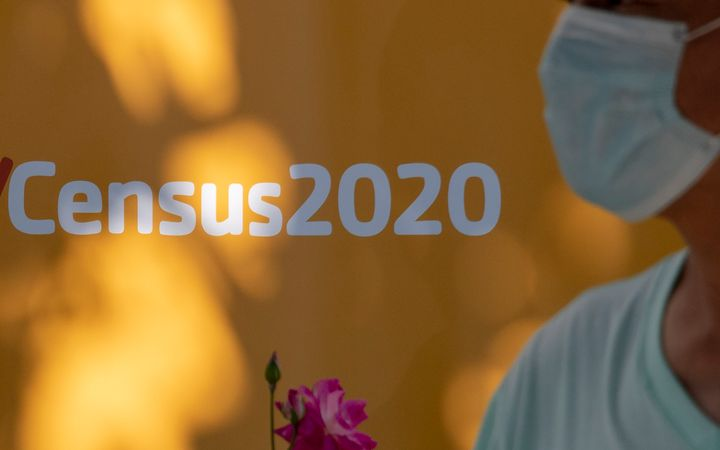 A man wearing a facemask walks past a sign encouraging people to complete the 2020 U.S. Census, in Los Angeles, California, A