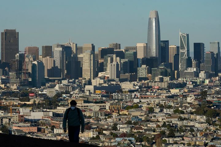 In this Dec. 7, 2020, file photo, a person wearing a protective mask walks in front of the skyline on Bernal Heights Hill dur