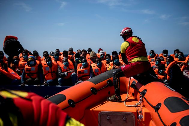 AT SEA - MARCH 29: A lifeguard from the Spanish NGO Open Arms approach a wooden boat to rescue 84 migrants...