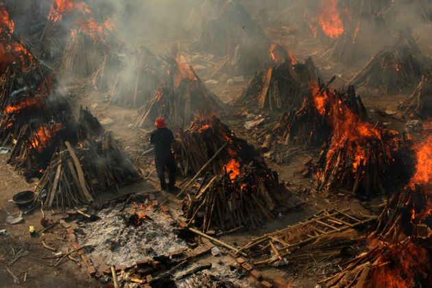 Un uomo aggiusta una pira funeraria durante una cremazione di massa delle vittime, morte a causa del...
