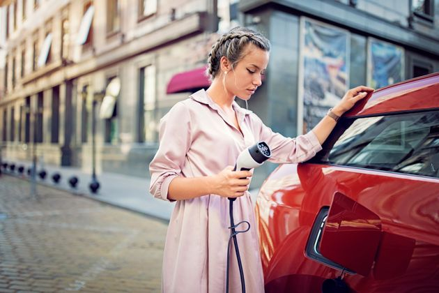 Young woman is charging her electric car in the