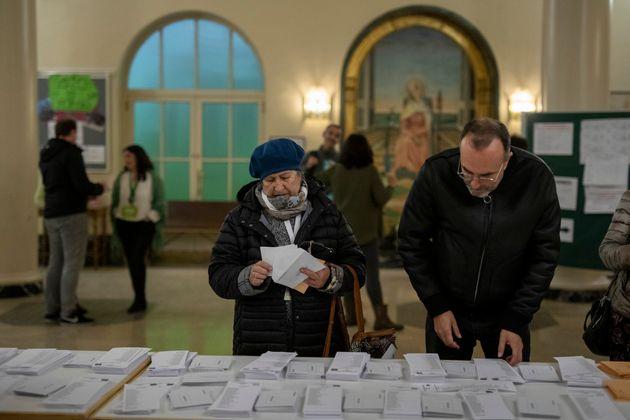 Unos madrileños preparan su voto, en los comicios de