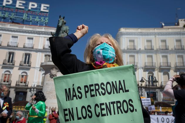 Una manifestante, con un cartel que pide 'más personal en los centros' sanitarios, durante una...