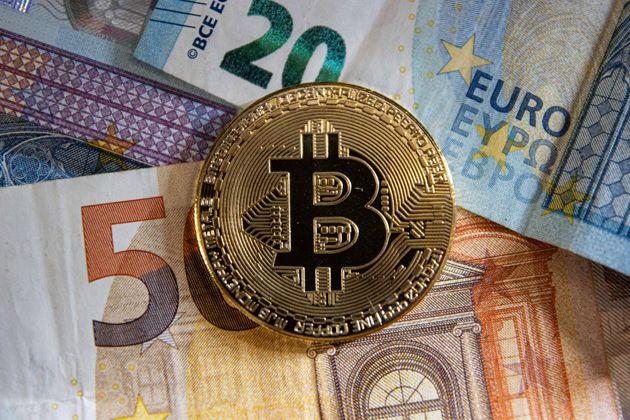 Bitcoin golden physical coin illustration on Euro banknotes of 20 and 50 euros. visual representations...
