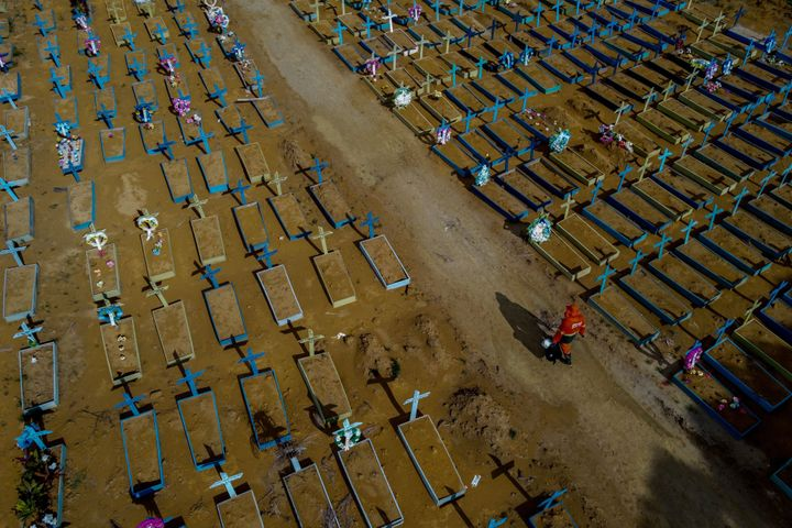 A gravedigger walks among COVID-19 victims' graves at the Nossa Senhora Aparecida cemetery in Manaus, Amazonas state, Brazil,