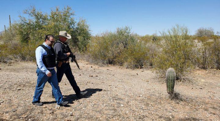 Arizona Attorney General Mark Brnovich, wearing a bulletproof vest, walks alongside an armed officer during a trip to the U.S