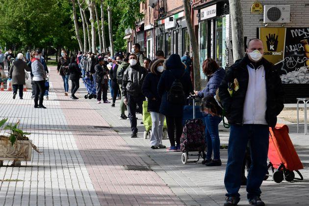 Varias personas en una cola para obtener comida del banco de alimentos en Aluche