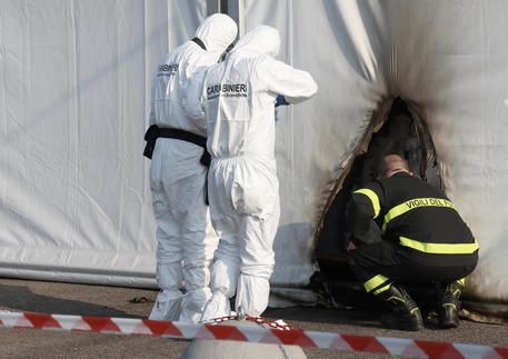 Forensic officers and firefighters inspect the scene where two petrol bombs were thrown at the building...