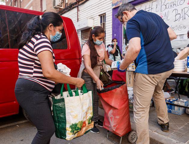 Dos mujeres recogen comida en una asociación de vecinos de