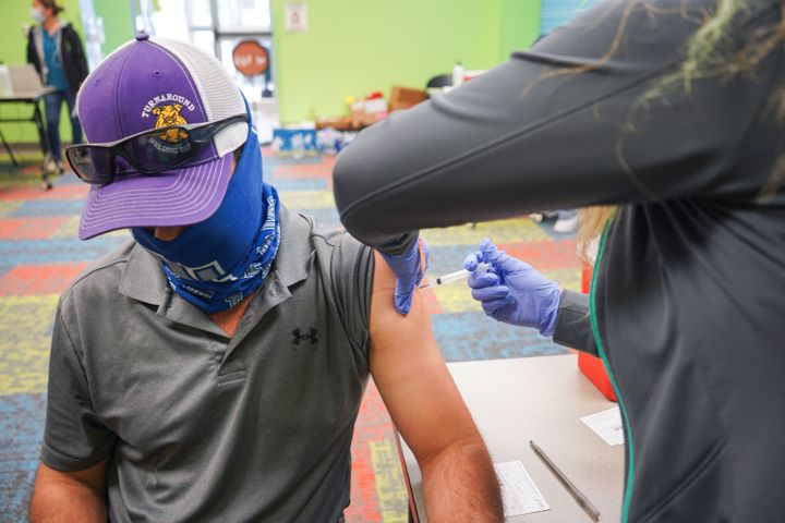 A health worker vaccinated a man on April 30, 2021 at the Pasadena Public Library in Pasadena, Texas.  (Photo by CECILE