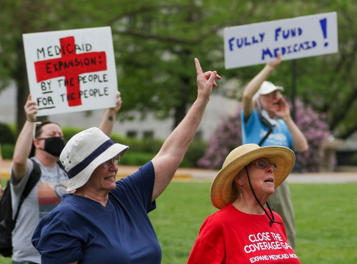 Maxine Horgan, left, and Barbara Nyden repeat the final chant of the Tuesday, April 27, 2021, Medicaid expansion rally at the