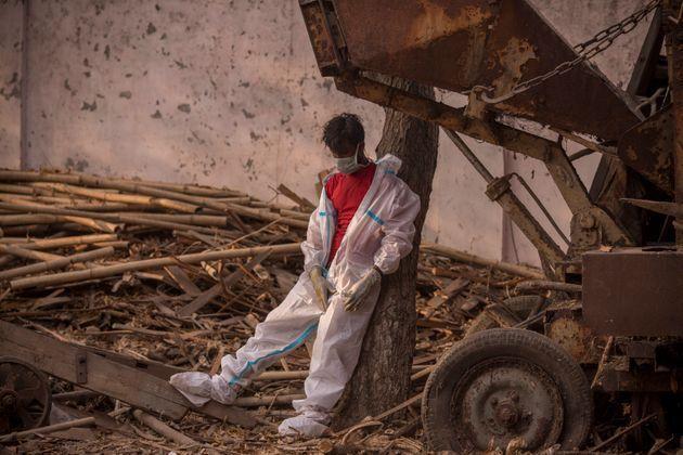 ニューデリーの集団火葬で、防護服を脱ぎ休憩する作業員。火葬場は昼夜を問わず稼働していると報道されている(Photo by Anindito Mukherjee/Getty