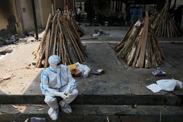 インド・ガジプールの火葬場。防護服を着ているのは、火葬を待つ家族(Photo by SAJJAD HUSSAIN/AFP via Getty