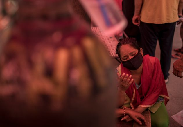 NEW DELHI, INDIA - MAY 01: A woman reacts as she accompanies her relative to receive free oxygen provided...