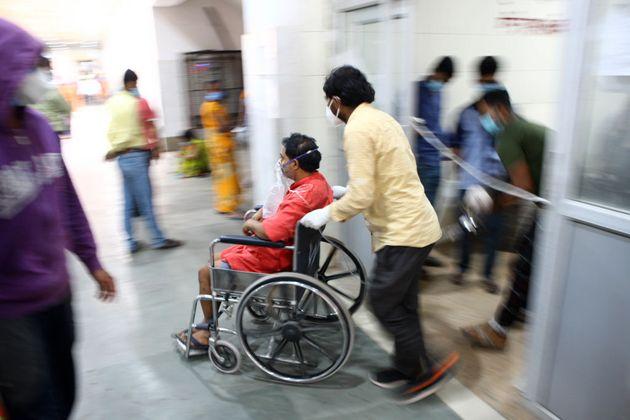 Un sanitario atiende a un paciente con coronavirus en India, con los hospitales