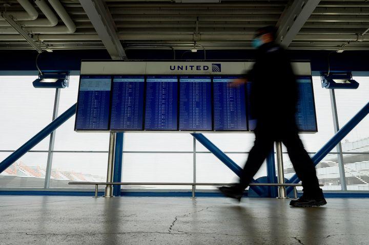 In this Oct. 14, 2020 file photo, a TSA staff wears mask as he walks past flight information screens show flight status infor