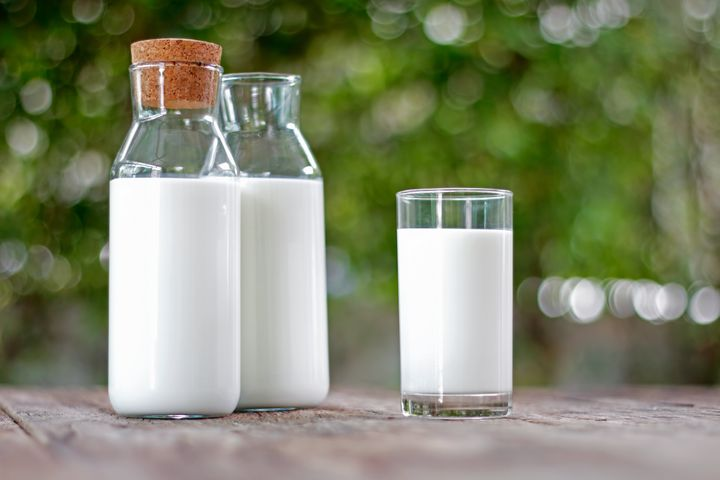 Milk bottle and milk glass on wooden table