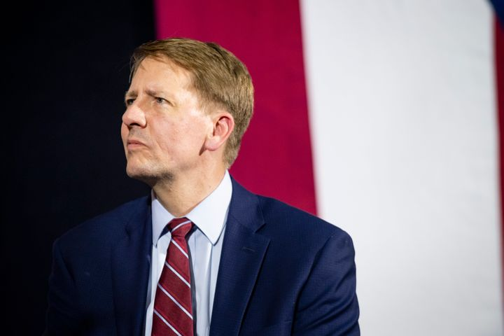 Richard Cordray listens while former President Barack Obama speaks during a campaign rally at CMSD East Professional Center G