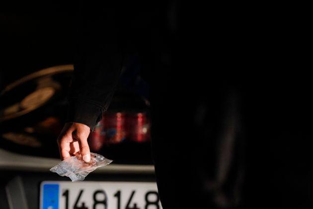 Une personne tient un sachet de résine de cannabis lors d'un contrôle du Peloton de surveillance...