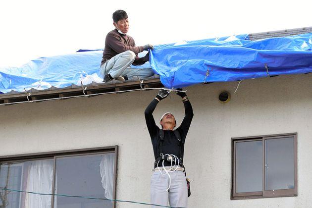 屋根にブルーシートを張る被災者の知人ら=2021年5月4日午後3時0分、牧之原市布引原、玉木祥子撮影