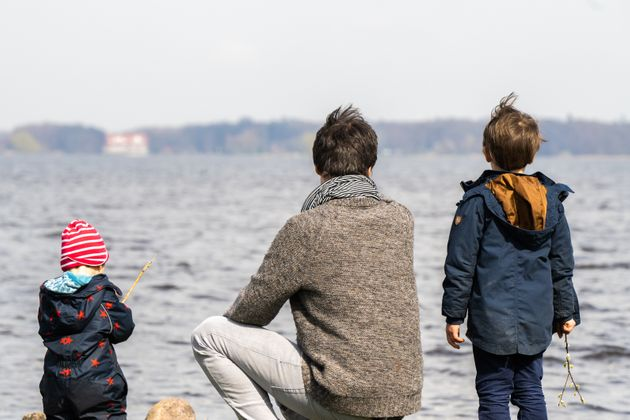 03 April 2021, Lower Saxony, Bad Zwischenahn: A father sits between his two sons in fine weather by the...
