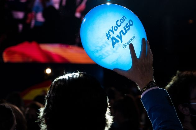 A supporter of the PP holds a balloon with the slogan 'Yo con Ayuso' at the Genoa party of this
