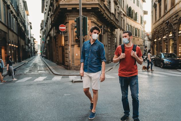 Two friends walking together in the city wearing protective face masks. They are wearing the masks due...