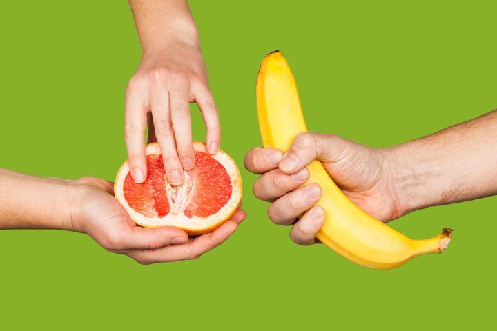 Mujer tocando su pomelo y hombre agarrando su plátano.