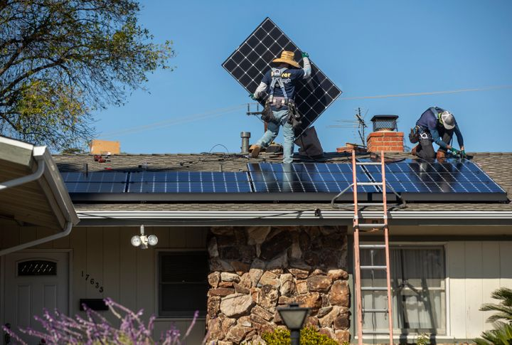 Workers install solar panels on a California home last year.