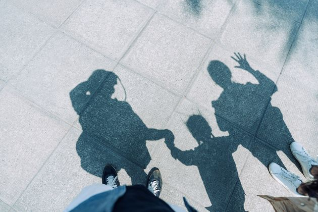 Shadow on gravel path of a loving family of three holding hands walking outdoors on a lovely sunny