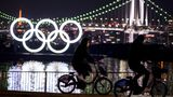 People cycle before the Olympic Rings at the Odaiba waterfront in Tokyo on February 6, 2021. (Photo by CHARLY TRIBALLEAU / AFP) (Photo by CHARLY TRIBALLEAU/AFP via Getty Images)