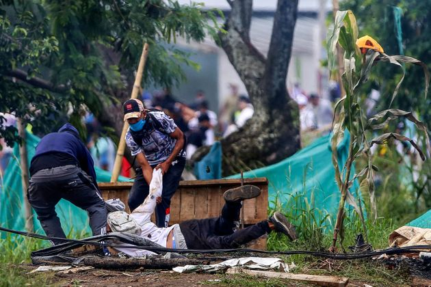 Dos manifestantes arrastran a un tercero, herido, tras una