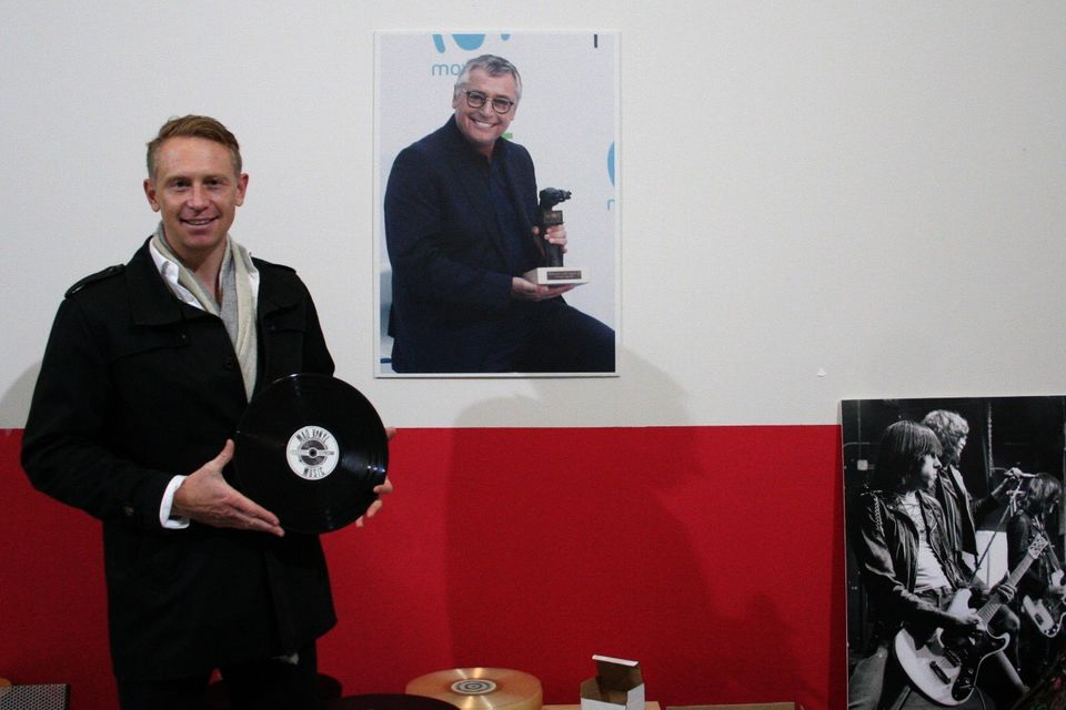 Liam Robinson, socio de Mad Vinyl Music, junto a un póster de su padre, Michael Robinson, socio...