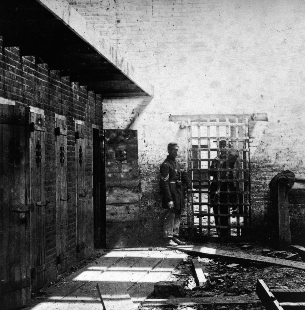 Two soldiers stand beside cells where enslaved Black people were confined in Alexandria, Virginia, circa 1861.