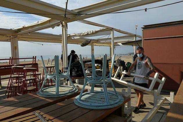 Varios trabajadores montando la terraza de un chiringuito de playa en
