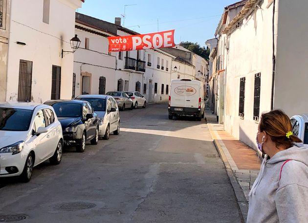 Una mujer cruza la calle principal de Fuentidueña de Tajo donde hay aún un cartel electoral del PSOE,...