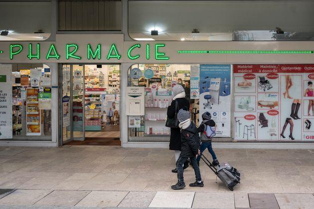 Une famille passant devant une pharmacie, quartier de La Défense, 15 mars 2021 à Puteaux....