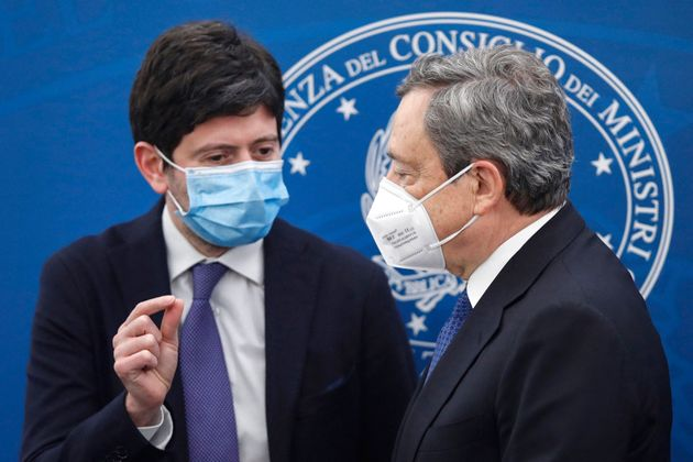 Italy's Prime Minister, Mario Draghi (R) and Italy's Health Minister, Roberto Speranza talk after holding...