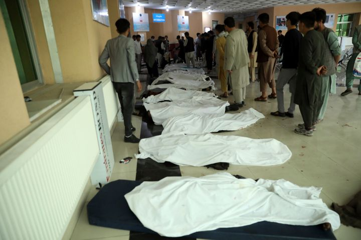 Afghan men try to identify the dead bodies at a hospital after a bomb explosion near a school west of Kabul, Afghanistan, Sat