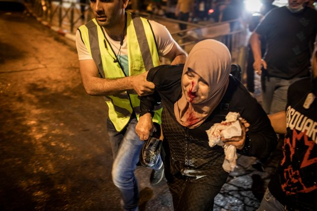 08 May 2021, Israel, Jerusalem: An injured woman is being helped during a demonstration against the planned...