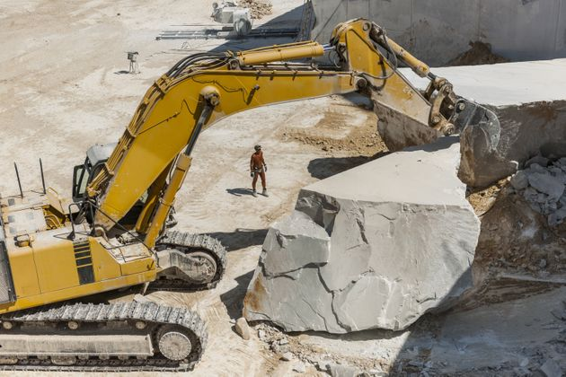 bulldozer at work in a marble quarry near Colonnata, the quarries provide raw material for various production...