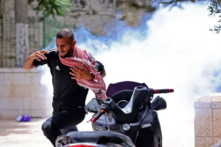 A Palestinian protester runs for cover from tear gas fired by Israeli security forces in Jerusalem's Old City on May 10, 2021