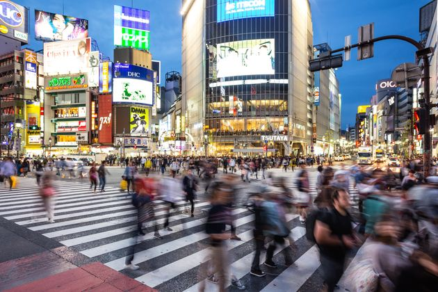 People, captured with blurred motion, walk through the famous Shibuya crossing in Tokyo, Japan