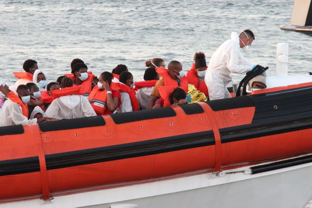 Rescued migrants are being transfered on a ginghy at the commercial port of Lampedusa on August 29, 2020...