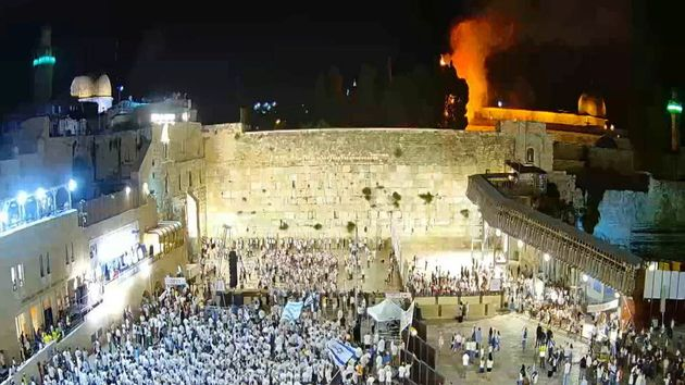 Israelis gather at the Western Wall as a blaze is seen in the background at the compound that houses...