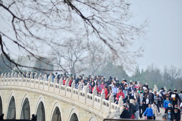 BEIJING, CHINA - MARCH 27, 2021 - Crowds of tourists enjoy flowers and take photos in front of the Happy...