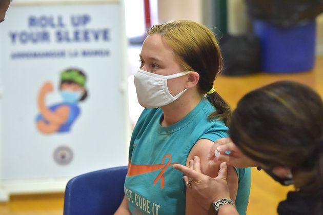 Una adolescente recibe uno de los viales de Pfizer en