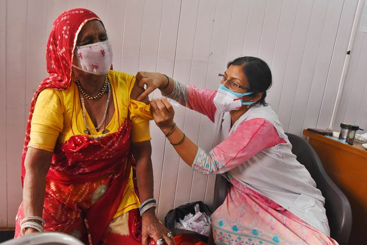A resident of a street artists' transit camp is inoculated against COVID-19 in New Delhi.