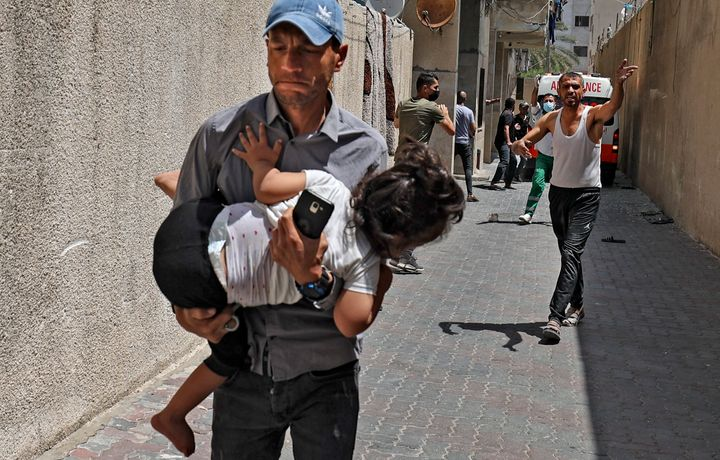 Palestinians evacuate a building targeted by Israeli bombardment in Gaza City on May 11, 2021.